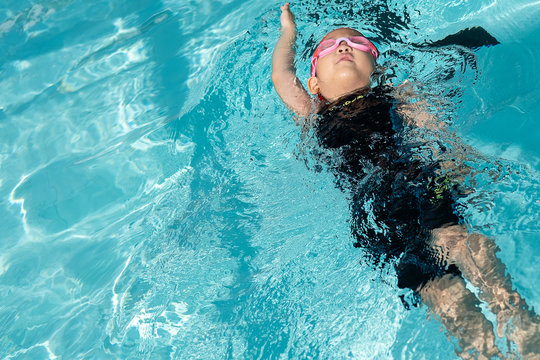 a girl learn how to swim in swimming class