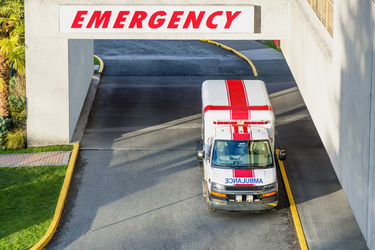 modern ambulance park parked near the emergency entrance to the hospital