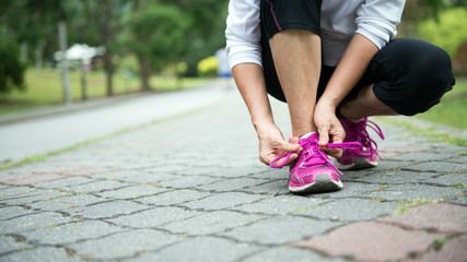 Woman jogger tighten her running shoe laces