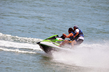 Tandem male riders on a speeding jet ski