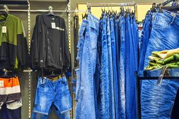 Row of hanged blue jeans in a shop. Clothes store. Shopping in fashion mall. Garments on hangers. Clothes on the store shelves