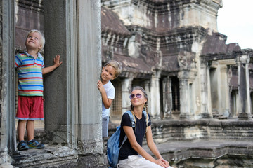 Happy tourists family, mother and two children in Angkor temple site, Cambodia. Concept travel, discovery, family Wall mural