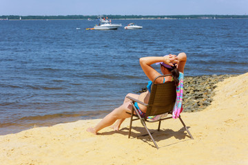 Side view of woman sitting on chair the beach. Young woman in bikini is relaxing on the seaside.