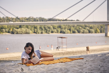 one young girl, relaxing reading a book outdoors, casual clothes, sunny day, laying on blanket, on sandy beach. unrecognizable people in background, lifeguard tower, river, trees, coast, bridge.