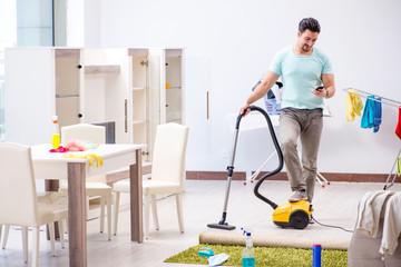 Young man husband doing vacuuming at home