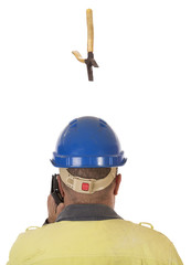 A tool falling from height towards a workers head which is protected by a safety helmet.