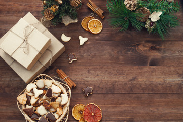 Christmas decoration, gift boxes, dry oranges, cinnamon and Christmas wreath frame background, top view with copy space on brown  wood table surface.