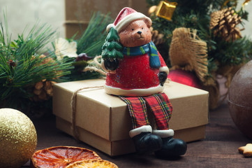 Christmas background, teddy bear sitting on a gift box with Christmas tree.