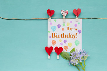 Happy birthday card with red heart clip and purple flower on blue background