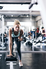 attractive caucasian woman workout with dumbbells and equipment exercises in gym fit and firm concept