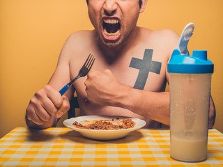 Young fitness man eating mince and protein shake