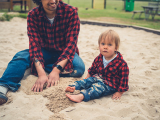 Father and son in identical clothes sitting in sandpit