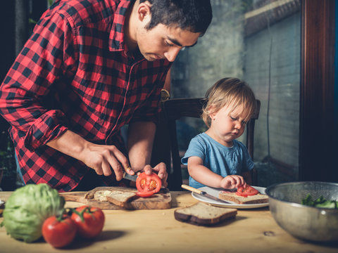 Father and toddler making sandwiches