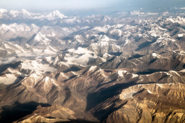 Beautiful sandstone Himalayan mountains with snow in summer season. View from the airplane of Leh - Ladakh, Northern India.