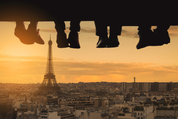 Underside view of dangling Four people  legs with wearing trekking shoes sitting  on the edge of wooden board-walk against  a background of Eiffel tower.