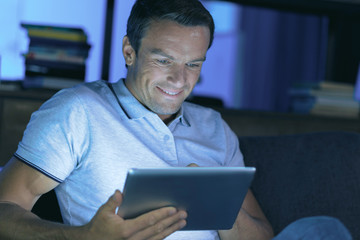 Browsing the Internet. Happy cheerful nice man holding a tablet and browsing the Internet while resting at home