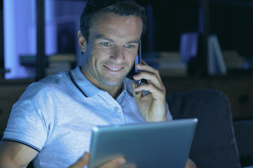 Distance communication. Cheerful positive handsome man holding his smartphone and making a call while using a tablet