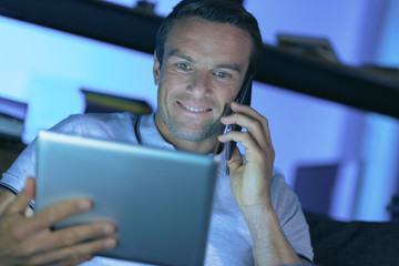 Electronic device. Positive joyful handsome man looking at the tablet screen and smiling while talking on the phone