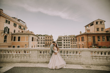 Young newly married couple  posing in Rome with beautiful and ancient architecture in the background