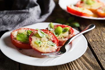 Tomatoes baked under Parmesan with fresh basil
