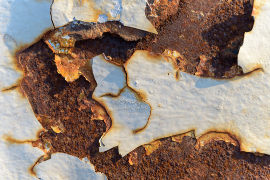 Pintura desconchada sobre metal oxidado