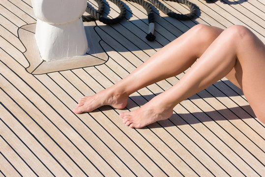 Women's feet the deck of the ship. A young woman sunbathes on the sun
