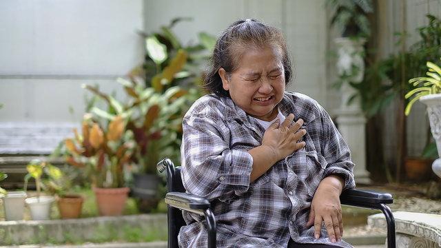Elder woman patient pain in her heart on wheelchair