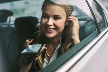 Businesswoman making phone call in cab Fototapete
