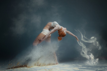 Keuken foto achterwand People Dancing in flour concept. Redhead beauty female girl adult woman dancer in dust / fog. Girl wearing white top and shorts making dance element in flour cloud on isolated grey black background
