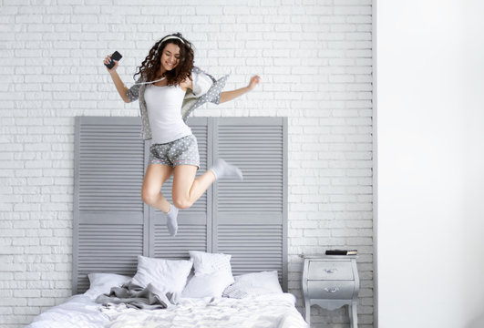 Happy girl woman female adult with curly hair and grey pajamas with hearts listening to music and jumping on her bed with pillows in the room with brick wall and grey bedside table. Happy lifestyle