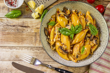 Pasta Conchiglioni with mushrooms in a vintage bowl on concrete background.