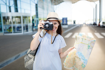 Young smiling traveler tourist woman take pictures on retro vintage photo camera, holding paper map at international airport. Female passenger traveling abroad on weekends getaway. Air flight concept.