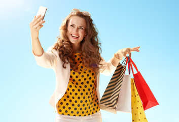 happy trendy woman shopper taking selfie with phone against blue sky