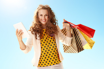 woman with shopping bags with tablet PC against blue sky