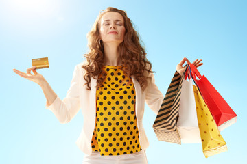 happy young woman with shopping bags and credit card doing yoga against blue sky