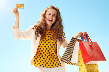 woman with shopping bags showing credit card against blue sky
