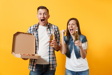 Overjoyed couple woman man sport fan cheer up support team hold beer bottle italian pizza in cardboard flatbox do winner gesture scream isolated on yellow background. Sport family leisure lifestyle.