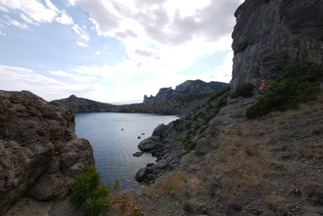 The wide bay is surrounded by high Crimean rocks covered with grass