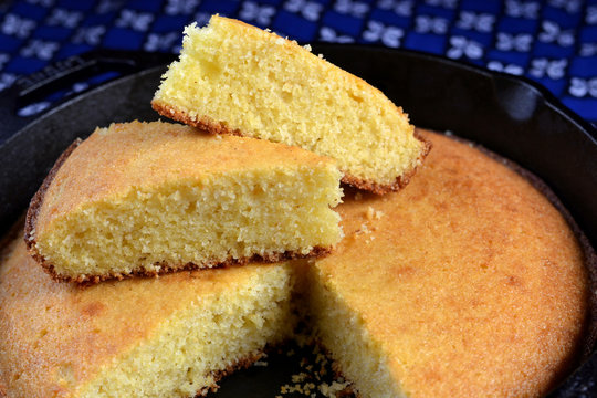 Homemade buttermilk cornbread served in a cast iron frying pan: close up, profile, selective focus.
