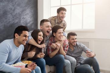 Happy friends watch film on the sofa