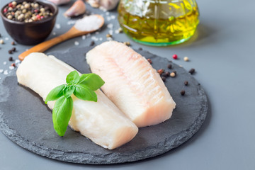 Fresh raw cod fillet with spices, pepper, salt, basil on stone plate, horizontal, copy space