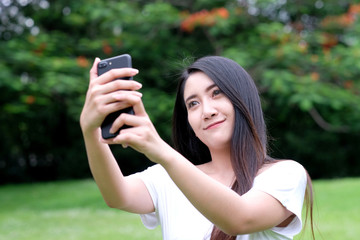Young asian woman using smartphone to selfie her portrait at nature park background, poeple and technology, lifestyle, travel blogger