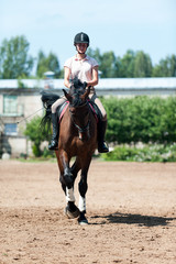 Teenage girl equestrian riding horseback on arena at sport training