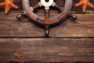 Ship's steering wheel, shells and brown fishing net on wooden table