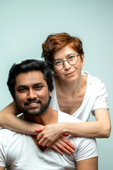 two mixed race friends posing to the camera. people are in love. just married couple in white T-shirts. warm relationship between woman and man, wife and husband with different nationalities