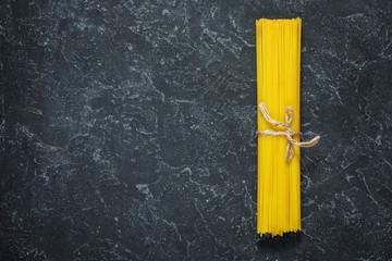 Bundle of Italian spaghetti pasta tied with string lying on dark stone background