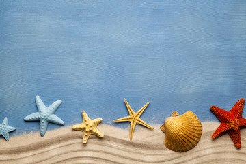 Summertime background - beach sand and seashells on blue table