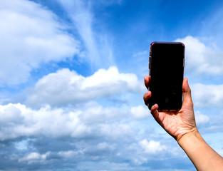 Hand holding black phone on blue sky