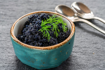 Black lumpfish caviar in a small pot on dark backgournd