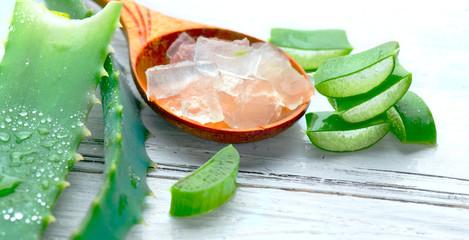 Fotoväggar - Aloe Vera gel closeup on white wooden background. Organic sliced aloevera leaf and gel, natural organic cosmetic ingredients for sensitive skin, alternative medicine. Skincare concept